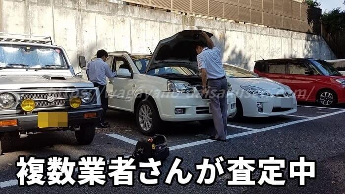 複数の業者さんが愛車を査定している写真
